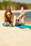 Summer vacation Girl with phone tanning on beach. Summer vacation. Sexy girl in bikini sunbathing tanning on the beach. Young woman relaxing with mobile phone on Stock Image