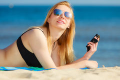 Summer vacation Girl with phone tanning on beach Stock Photo