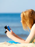 Summer vacation Girl with phone tanning on beach. Summer vacation. Sexy girl in bikini sunbathing tanning on the beach. Young woman relaxing with mobile phone on Stock Images