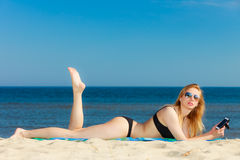 Summer vacation Girl with phone tanning on beach Stock Photography