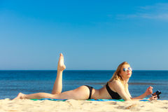 Summer vacation Girl with phone tanning on beach. Summer vacation. Sexy girl in bikini sunbathing tanning on the beach. Young woman relaxing with mobile phone on Stock Photos