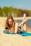 Summer vacation Girl with phone tanning on beach. Summer vacation. Sexy girl in bikini sunbathing tanning on the beach. Young woman relaxing with mobile phone on Royalty Free Stock Images