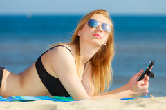 Summer vacation Girl with phone tanning on beach Royalty Free Stock Photos