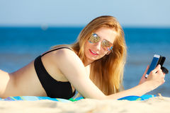 Summer vacation Girl with phone tanning on beach Royalty Free Stock Image