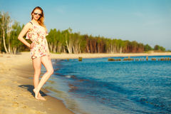 Summer vacation. Girl standing alone on the beach. Stock Photography