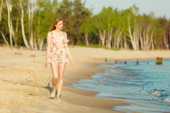 Summer vacation. Girl walking alone on the beach. Stock Images