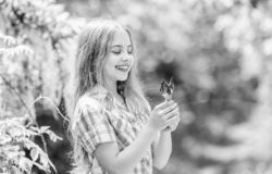 Summer vacation. Green environment. happy child hold iris flower. little girl and iris flower. Natural beauty. Childhood stock photo
