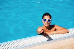 Summer vacation happiness and relax in swimming pool. Happy woman on summer vacation pointing at camera in swimming pool Stock Photo