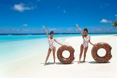 Summer Vacation. Happy free two women with donut float mattress enjoying exotic beach by turquoise water seaside. Maldives island. Paradise background stock images