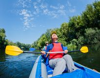 Summer vacation - Happy girl with her mother kayaking on river. Royalty Free Stock Image