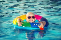Happy little boy playing with colorful inflatable ring in outdoor swimming pool on hot summer day and drinks a cocktail. stock photo