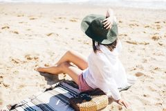 Summer vacation. Happy young boho woman relaxing and enjoying sunny warm day at ocean. Space for text. Stylish hipster girl in hat. Sitting on beach with straw royalty free stock photos