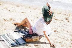 Summer vacation. Happy young boho woman relaxing and enjoying sunny warm day at ocean. Space for text. Stylish hipster girl in hat. Sitting on beach with straw stock photography