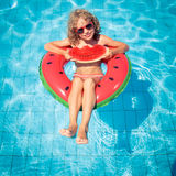 Summer vacation and healthy eating concept. Child with watermelon outdoor. Kid having fun in swimming pool. Summer vacation and healthy eating concept Stock Image