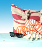 Summer vacation holiday gear with red and white strip beach bag, flip flop things, shell and sunglasses Stock Images