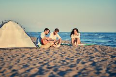 Summer, vacation, holiday, happy people concept - friends relaxi. Summer, vacation, holiday, happy people concept- group of friends relaxing with playing guitar royalty free stock photos