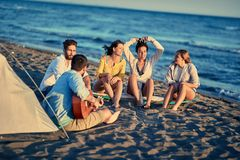 Summer, vacation, holiday, happy people concept- Happy friends t. Summer, vacation, holiday, happy people concept- Group of happy friends together relaxing with royalty free stock photo