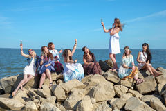 Summer vacation, holidays, travel and people concept - group of smiling young women on beach Royalty Free Stock Photos