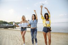 Summer vacation, holidays, travel and people concept - group of smiling young women dancing on beach. Royalty Free Stock Photos