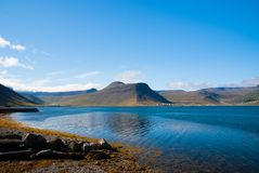 Summer vacation in isafjordur, iceland. Hilly coastline on sunny blue sky. Mountain landscape seen from sea. Discover. Wild nature on scandinavian island Stock Photo