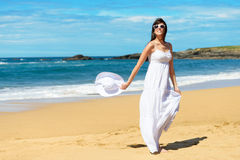 Summer vacation joyful woman walking. Joyful woman in white dress enjoying and dancing on the beach during summer lifestyle walk. Relax travel and vacation Stock Images