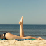 Summer vacation. Legs of sunbathing girl on beach Royalty Free Stock Images