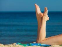 Summer vacation. Legs of sunbathing girl on beach stock photo