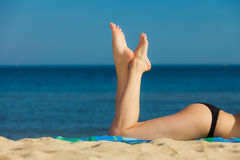 Summer vacation. Legs of sunbathing girl on beach stock photos