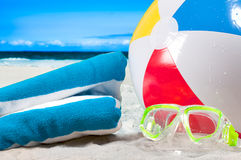 Summer vacation. Mask goggles and color ball on beach background stock image