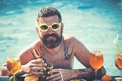 Summer vacation at Miami beach or Maldives. Pool party, vitamin and dieting. Man swimming and drink alcohol. Cocktail stock photography