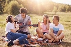 Summer, vacation, music and recreation time concept. Cheerful four friends or classmates have picnic outdoor, sing songs to guitar. Drink energetic beverages stock photo