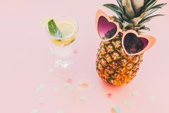 Summer vacation and party concept. stylish pineapple in pink sun. Glasses and mojito cocktail drink on trendy pink paper background with confetti. space for text Royalty Free Stock Image
