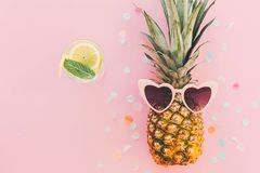 Summer vacation and party concept. stylish pineapple in pink sun. Glasses and cocktail drink on trendy pink paper background with confetti. flat lay. space for Royalty Free Stock Photos
