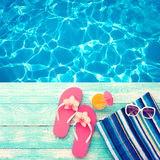 Summer vacation. Pink sandals by swimming pool Royalty Free Stock Photos