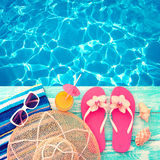 Summer vacation. Pink sandals by swimming pool Royalty Free Stock Images