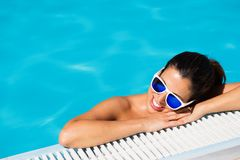 Summer vacation and relax in swimming pool. Relaxed cheerful woman in swimming pool. Summer relaxing vacation and leisure concept. Tanned female sunbathing into Royalty Free Stock Photos