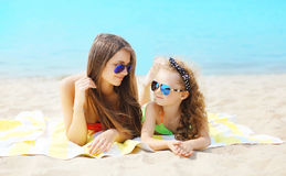 Summer vacation, relaxation, travel concept - portrait mother and child lying on beach Stock Photography