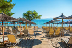 Summer vacation. Resort beach. Sun chairs on the beach with sea in background. Summer holiday / vacation. Xenia Golden Beach, Paliouri, Chalkidiki, Greece on a Stock Images