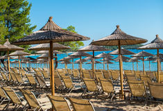 Summer vacation. Resort beach. Sun chairs on the beach with sea in background. Summer holiday / vacation. Xenia Golden Beach, Paliouri, Chalkidiki, Greece on a Royalty Free Stock Photography