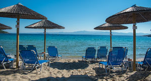 Summer vacation. Resort beach. Sun chairs on the beach with sea in background. Summer holiday / vacation. Xenia Golden Beach, Paliouri, Chalkidiki, Greece on a Royalty Free Stock Photo