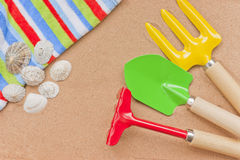 Summer vacation, sand, seashells, towel, toys. Summer vacations at the seaside: beach towel, sand, seashells and colourful toys royalty free stock images