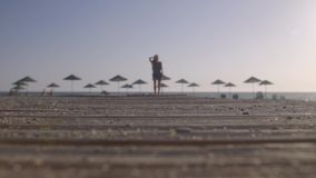 Woman Walking at the Beach. Summer vacation scene. Empty beach with lots of sun umbrella silhouettes on the ocean coast. Fit slim figure of a young beautiful stock footage