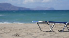 Empty Chaise Longue Under Sun Umbrella on the Ocean Coast. Summer vacation scene. Empty chaise longues under sun umbrella on the ocean coast. Beach with white stock video footage