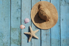 Summer vacation scene. Hat, seashells and starfish on the wood blue background Royalty Free Stock Photos
