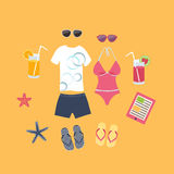 Summer vacation set of icons. With a mans shorts, t-shirt and slip slops and a female swimsuit and sandals with glasses of cocktail and starfish on yellow beach Royalty Free Stock Images