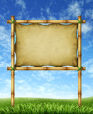 Summer Vacation Sign. Vacation sign billboard made of bamboo sticks with blank stretched leather canvas for your text on a bright blue sky and green grass Royalty Free Stock Images