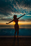 Summer Vacation. Silhouette of beauty dancing woman on sunset near the pool with ocean view. Royalty Free Stock Photos