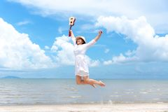 Summer Vacation. Smelling asian women relaxing , jumping and playing an ukulele on the beach, so happy and luxury in holiday summe royalty free stock photography