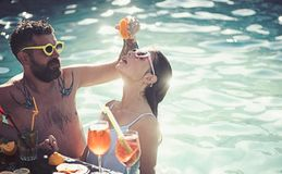Summer vacation and swimming at sea. couple of bearded man and woman with cocktail and fruit in miami. Cocktail at man. Summer vacation and swimming at sea stock photography