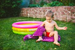 Summer vacation theme. A small 3 year old Caucasian boy playing in the backyard of a house on the grass near a round inflatable co royalty free stock images